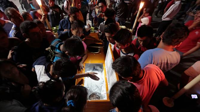 People gather around the coffin of Julio Cesar Ramirez during his funeral at the Ayotzinapa Teacher Training College in Guerrero