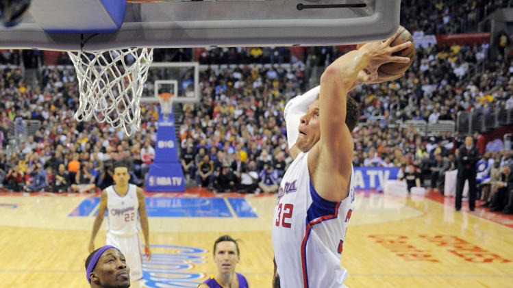 Los Angeles Clippers forward Blake Griffin, right, goes up for a dunk as Los Angeles Lakers center Dwight Howard, left, and guard Steve Nash, center, look on during the second half of their NBA basketball game, Friday, Jan. 4, 2013, in Los Angeles. The Clippers won 107-102.  (AP Photo/Mark J. Terrill)