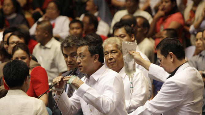 Sick Filipino Congressman Romero Federico Quimbo, center, is accompanied by a doctor, as he states his vote on a landmark law that would provide government funding for contraceptives and sexuality classes during a session at the Philippine Congress in suburban Quezon City, north of Manila, Philippines on Monday, Dec. 17, 2012. Philippine legislators passed the law despite strong opposition by the dominant Roman Catholic Church and its followers, some of whom threatened to ask the Supreme Court to thrash the legislation. (AP Photo/Aaron Favila)
