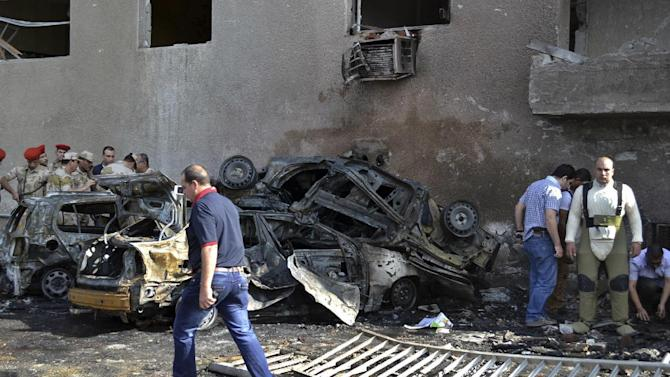 Security officials and an explosive expert, second right, examine the site of a car bomb in the Suez Canal city of Ismailia, Egypt, Saturday Oct. 19, 2013. A car bomb exploded Saturday near an Egyptian military intelligence compound in the Suez Canal city of Ismailia, wounding several soldiers, security officials said, as militants appear to be expanding the scope of attacks beyond the restive Sinai Peninsula. (AP Photo)