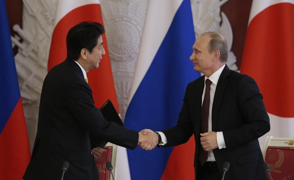 Russian President Vladimir Putin, right, and visiting Japanese Prime Minister Shinzo Abe shake hands after they exchanged documents in Moscow's Kremlin, Monday, April 29, 2013. Abe is in Russia on an official visit. (AP Photo/Ivan Sekretarev, pool)
