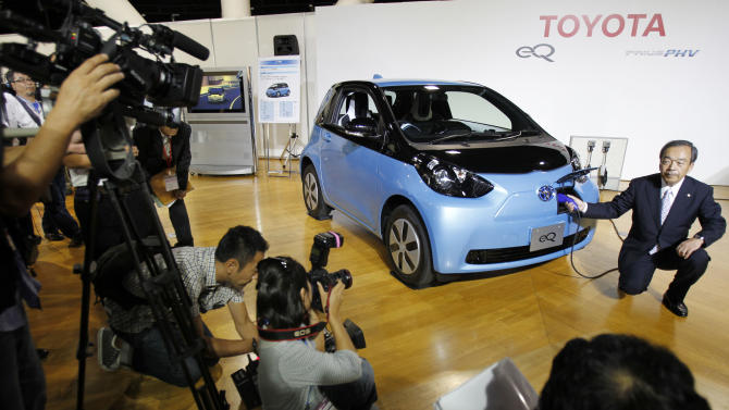 "Toyota Motor Corp. Vice Chairman Takeshi Uchiyamada poses for photographers as he puts a plug to the newly-developed compact electric vehicle ""eQ"" during a press conference in Tokyo Monday, Sept. 24, 2012. Toyota is boosting its green vehicle lineup, with plans for 21 new hybrids in the next three years, a new electric car later this year and a fuel cell vehicle by 2015 in response to growing demand for fuel efficient and environmentally friendly driving. (AP Photo/Koji Sasahara)"