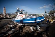 A boat washed ashore by Typhoon Haiyan stands in the middle of a crossroad in Tacloban, on the eastern island of Leyte, on November 15, 2013