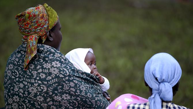 A woman carrying a child waits for Pope Francis to arrive to lead a mass in Kampala