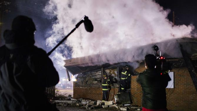A news crew films as members of the Ferguson Fire Department respond to a flare up in a building that had been destroyed after a night of rioting in Ferguson