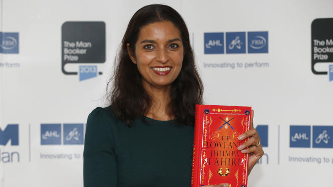 FILE - In this Oct. 13, 2013 file photo, author Jhumpa Lahiri poses with her book 'The Lowland' in London. Lahiri, Thomas Pynchon, and George Saunders were among the finalists Wednesday, Oct. 16, 2013 for the National Book Awards. A month after releasing long-lists of 10 in each of the four competitive categories, the National Book Foundation announced the five remaining writers for fiction, nonfiction, poetry and young people's literature. Winners receive $10,000 and will be announced at a dinner ceremony in Manhattan on Nov. 20. (AP Photo/Sang Tan)