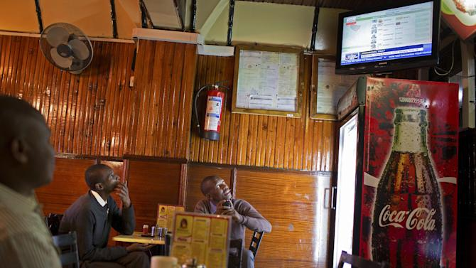 Kenyans watch the provisional results for the presidential candidates as they are announced on television, at a restaurant in downtown Nairobi, Kenya Tuesday, March 5, 2013. Kenyan presidential candidate Uhuru Kenyatta, who faces charges at the International Criminal Court, took an early lead Tuesday as votes were counted the day after the country's presidential election. (AP Photo/Mackenzie Knowles-Coursin)