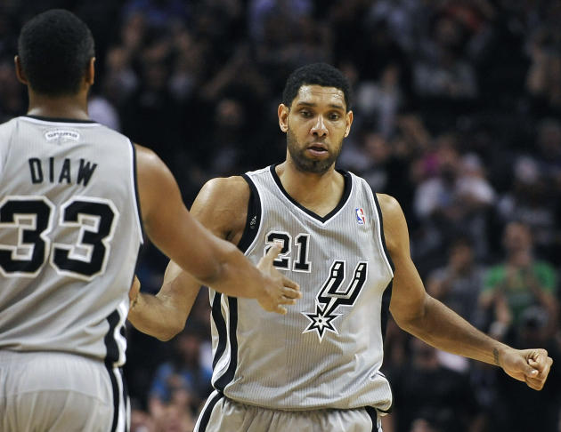 San Antonio Spurs forward Tim Duncan, right, is congratulated by Spurs' Boris Diaw, of France, after scoring in the final seconds of an NBA basketball game against the Sacramento Kings on Saturday