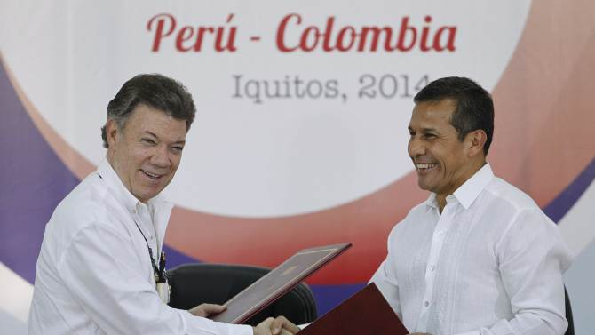 Colombia's President Juan Manuel Santos and Peru's President Ollanta Humala shake hands while exchanging agreements during the First Peru-Colombia Binational Cabinet meeting at a military base in the Amazonian city of Iquitos