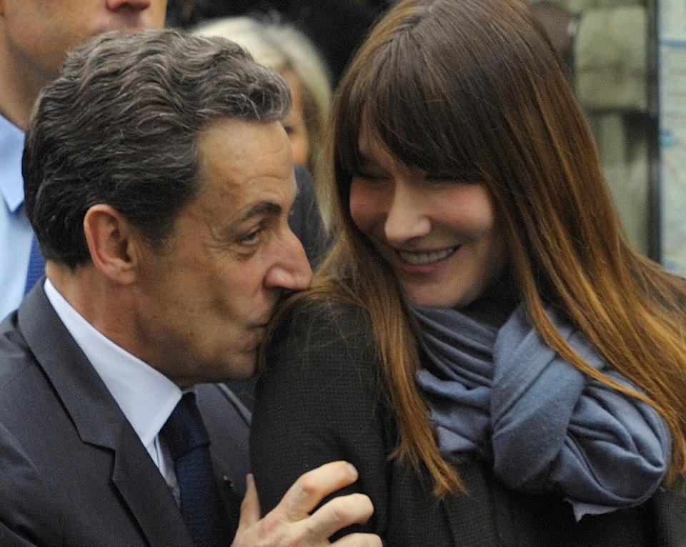 French President and UMP candidate Nicolas Sarkozy kisses his wife Carla Bruni-Sarkozy as they are greeted by supporters after casting their votes in the second round of French presidential elections in Paris, France, Sunday, May 6, 2012. (AP Photo/Philippe Wojazer, Pool)