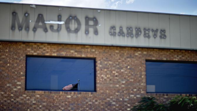 "In this Aug. 22, 2012 photo, an American flag is reflected in the window of a closed carpet store along the Interstate 75 corridor of carpet businesses in Dalton, Ga. Collapsing industry or not, Dalton city officials are still the proud owners of the label ""Carpet Capital of the World,"" but what they aren't happy about is the most recent label: The city that is leading the nation in the number of job losses per capita this year. The city that makes nearly 75 percent of the nation's flooring has lost 4,600 jobs between June 2011 and June 2012 according to the United States Bureau of Labor Statistics. Dalton's economy hit bottom in 2009 with the collapse of the housing market, taking hundreds of distributor business and support services down with it and struggling to recover in recent years. (AP Photo/David Goldman)"
