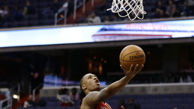 Portland Trail Blazers guard Damian Lillard shoots between Washington Wizards forward Kevin Seraphin, left, from France, and guard A.J. Price during the first half of an NBA basketball game Wednesday, Nov. 28, 2012, in Washington. (AP Photo/Alex Brandon)