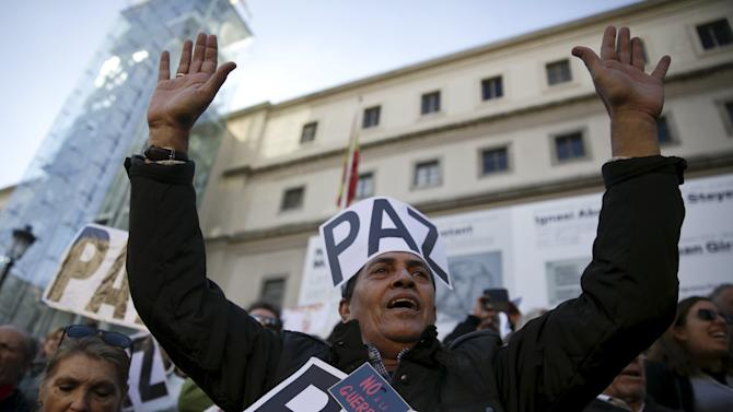 "A man with placards reading ""Peace"" and ""No War"" shouts slogans during a protest against militant attacks and war, in Madrid, Spain"