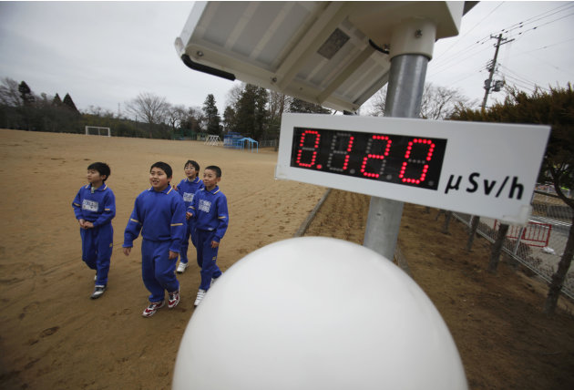 Students walk near a geiger counter at Omika Elementary School in Minamisoma