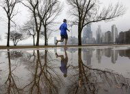 A lone jogger makes his way along Lake Michigan in unseasonably warm temperatures at Chicago's North Ave. Beach Tuesday, Jan. 29, 2013, in Chicago. Unseasonably warm temperatures broke records in the Chicago area with thunderstorm expected to usher in freezing temperatures and snow Wednesday. (AP Photo/Charles Rex Arbogast)