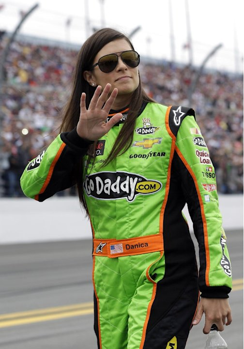 Danica Patrick waves to fans as she walks down pit road before the start of the NASCAR Daytona 500 Sprint Cup Series auto race at Daytona International Speedway, Sunday, Feb. 24, 2013, in Daytona Beac