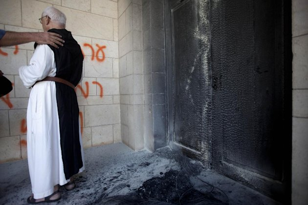 "A catholic priest looks at anti-Christian graffiti written in Hebrew "" at the Latrun Trappist Monastery where Israeli police say vandals overnight have spray-painted anti-Christian and pro-settler gra"
