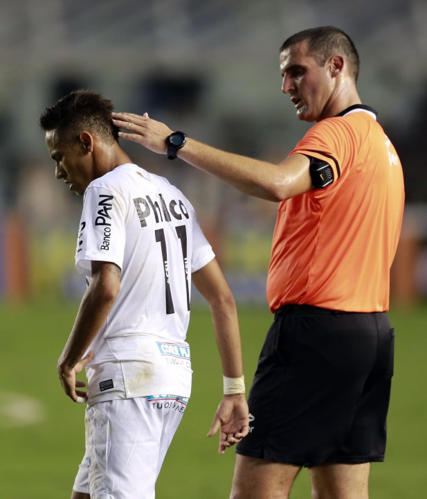 Neymar of Santos is comforted by referee Gulherme Ceretta during their Sao Paulo state soccer league final match against Corinthians in Santos