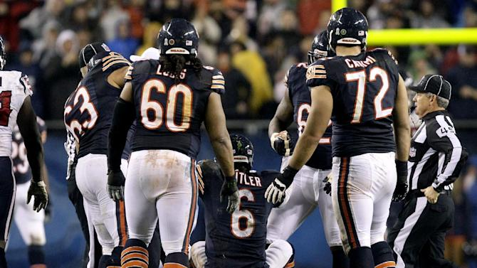 Chicago Bears quarterback Jay Cutler (6) is helped up by teammates after he threw an illegal forward pass and was hit by Houston Texans linebacker Tim Dobbins during the first half of an NFL football game, Sunday, Nov. 11, 2012, in Chicago. Dobbins was penalized for unnecessary roughness on the play. Cutler did not return in the second half after suffering a concussion. (AP Photo/Nam Y. Huh)