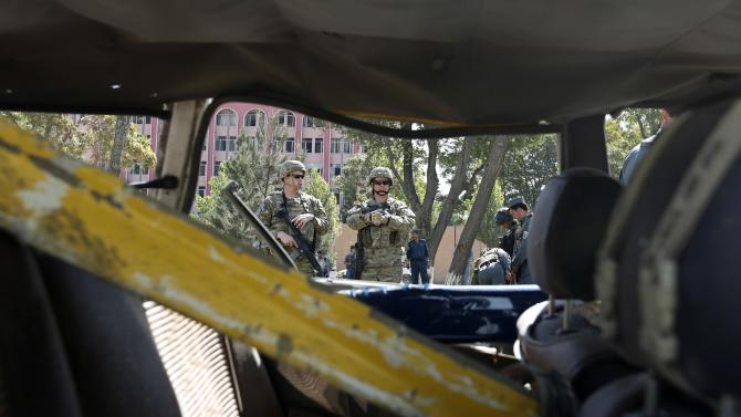 U.S. troops keep watch near a damaged vehicle at the site of a suicide attack in Kabul
