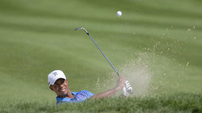 Tiger Woods hits out of the sand trap on the fourth hole during the second round of the Deutsche Bank Championship PGA golf tournament at TPC Boston in Norton, Mass., Saturday, Sept. 1, 2012. (AP Photo/Stew Milne)