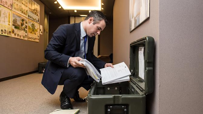 FOR STORY - EUROPE'S TRAVELING PARLIAMENT - Germany's Member of the European Parliament Alexander Alvaro, packs his documents, at the European Parliament building, in Brussels, on Friday, Feb. 1, 2013, ready to move to Strasbourg. The EU set up two parliaments, one at headquarters in Brussels, Belgium, and the other in Strasbourg, France, so in a whirl of trunks, trolleys and backpacks, hundreds of European Union parliamentarians and their staff move some 350-kilometer (220-mile) across the continent for four days of meetings, at an annual cost of about euro 1.3 billion (US dlrs 1.8 billion). (AP Photo/Geert Vanden Wijngaert)
