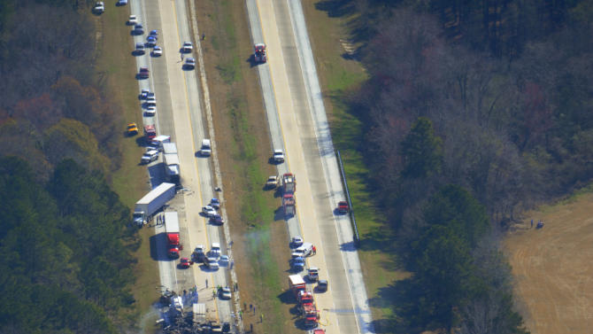 Cars and trucks are strewn along the road after a major pileup on Interstate 16 near the Jeffersonville, Ga. early Wednesday morning Feb. 6, 2013.   More than two dozen vehicles collided in a fiery pileup on the foggy Georgia interstate killing at least three people and leaving several others hurt, officials said.  (AP Photo/The Macon Telegraph, Woody Marshall)