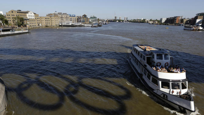 A passenger boat passes a reflection of Olympic rings on the River Thames in London,  Monday, July 23, 2012. The summer Olympics in London will start on Friday July 27. (AP Photo/Kirsty Wigglesworth)