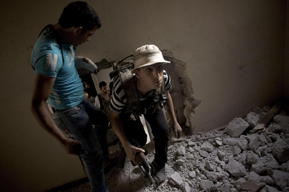 In this Saturday, Oct. 20, 2012 photo, Free Syrian Army fighters advance towards Syrian Army positions by passing through holes between adjoining houses during an operation in the Amariya district of Aleppo, Syria. (AP Photo/ Manu Brabo)