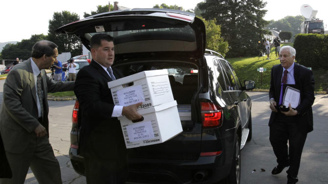 Former Penn State University assistant football coach Jerry Sandusky, right, arrives with his attorney Joe Amendola, left, as case files are unloaded at the Centre County Courthouse in Bellefonte, Pa., Wednesday, June 20, 2012. Sandusky is charged with 51 counts of child sexual abuse involving 10 boys over a period of 15 years.  (AP Photo/Gene J. Puskar)