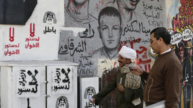 """Egyptian walk next to graffiti and Arabic writing that reads at left, """"no to the Muslim Brotherhood constitution,"""" in Tahrir Square in Cairo, Egypt,, Monday, Dec. 10, 2012. The Egyptian military on Monday assumed joint responsibility with the police for security and protecting state institutions until the results of a Dec. 15 constitutional referendum are announced. (AP Photo/Hassan Ammar)"""