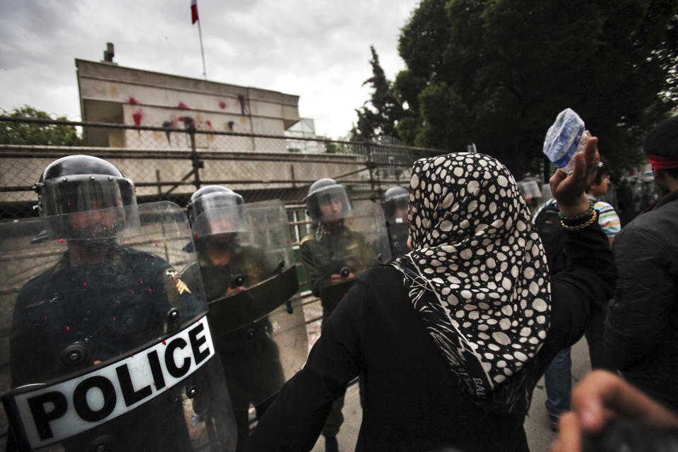 A female Iranian demonstrator throws a bottle at the Bahraini Embassy in Tehran, Iran, Saturday, April 30, 2011, in a gathering to show support for Bahraini opposition, as police officers protect the Embassy. (AP Photo/IIPA, Azin Haghighi)