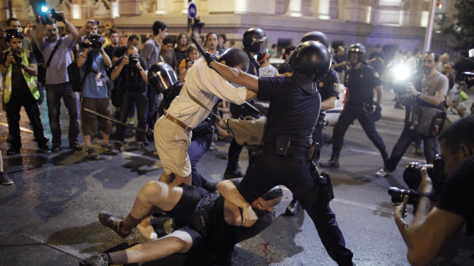 Police clash with protestors during a demonstration against the government in front of the People's Party headquarter in Madrid, Spain, Thursday, July 18, 2013. Spain's Prime Minister on Monday brushed off demands he should resign after text messages emerged showing he had a cozy relationship with a disgraced political party treasurer who amassed 47 million euros ($61 million) in secret Swiss bank accounts. The spectacle of alleged greed and corruption has enraged Spaniards hurting from austerity and sky high unemployment with no end in sight. (AP Photo/Andres Kudacki)