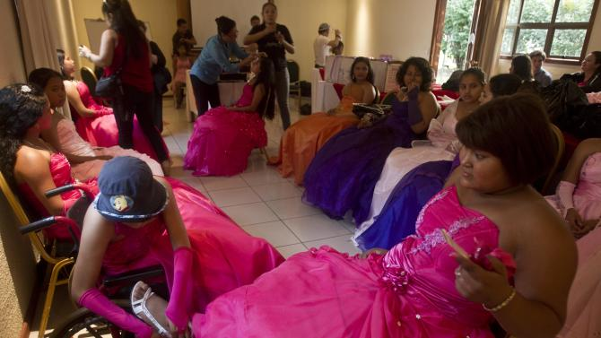 """Yamileth Barrera, left, a 16-year-old from San Jose de Bocay, on a wheelchair she uses because of bone cancer. ties the shoe of her friend Keyling Kenry, suffering from a Hodgkin's lymphoma, as they prepare for a """"quinceanera"""" party in Managua, Nicaragua, Saturday Sept. 21, 2013. For each of the past five years, Nicaragua's Association of Mothers and Fathers of Children with Cancer and Leukemia has put on a """"quinceanera"""" party for girls from poor, rural families, teens who have the added burden of dealing with cancer. This year's party feted 37 girls between ages 14 and 16 on Saturday night at a hotel in Nicaragua's capital.(AP Photo/Esteban Felix)"""