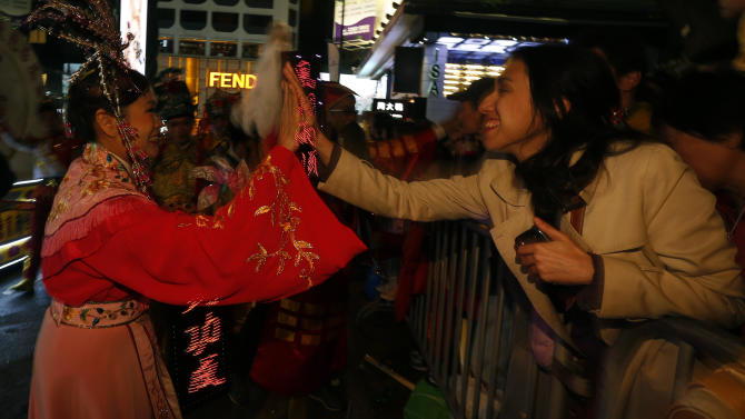 A spectator greets a Chinese dance performer during a Lunar New Year parade in Hong Kong