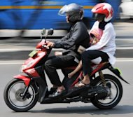 <p>This file photo shows an Indonesian family riding on a Honda motorcycle in Jakarta. Japan's Honda Motor said on Monday that first-half net profit more than doubled to $2.7 billion, but its shares dived as the automaker warned full-year results would be much weaker than forecast.</p>