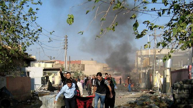 People evacuate a victim at the scene of a bomb attack in Kirkuk, 180 miles (290 kilometers) north of Baghdad, Iraq, Tuesday, Nov. 27, 2012. Three parked car bombs exploded Tuesday morning simultaneously in the city of Kirkuk, home to a combustible mix of Kurds, Sunni Arabs and Turkomen who all claim rights to the city, killing and wounding scores of people, police said. (AP Photo/Emad Matti)