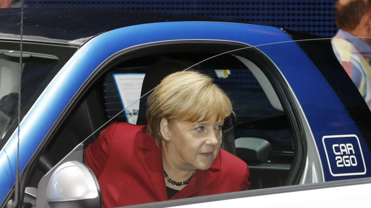 German Chancellor Angela Merkel disembarks from a Smart electric drive during her visit to the 65th Frankfurt Auto Show in Frankfurt, Germany, Thursday, Sept. 12, 2013. More than 1,000 exhibitors will show their products to the public from Sept. 12 through Sept. 22, 2013. (AP Photo/Michael Probst)