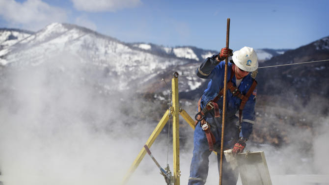 """In this March 29, 2013 photo, a worker checks a dipstick to check water levels and temperatures in a series of tanks at an Encana Oil & Gas (USA) Inc. hydraulic fracturing operation at a gas drilling site outside Rifle, Colorado. Hydraulic fracturing, or """"fracking,"""" can greatly increase the productivity of an oil or gas well by splitting open rock with water, fine sand and lubricants pumped underground at high pressure. Companies typically need several million gallons of water to frack a single well. In western Colorado, Encana says it recycles over 95 percent of the water it uses for fracking to save money and limit use of local water supplies. (AP Photo/Brennan Linsley)"""