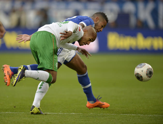 Bremen's Theodor Gebre Selassie of Czech Republic, left, and Schalke's Dennis Aogo challenge for the ball during the German Bundesliga soccer match between FC Schalke 04 and Werder Bremen in Gelsenkir