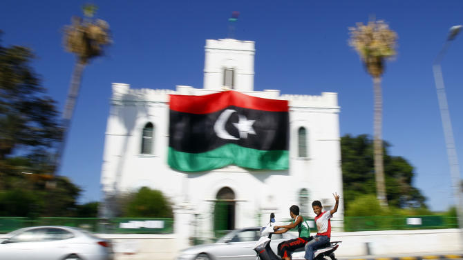 Libyan youth flash the V-Victory sign as they ride their motorcycle infront of Libya's flag of the former rebels on a building in Al Ajaylat, 120 km west of Tripoli, Libya, Wednesday, Sept. 7, 2011.  The new colours of the flag decorates a lot of streets and building after the six-month civil war that ended Gadhafi's 42-year rule and sent him into hiding. (AP Photo/Francois Mori)