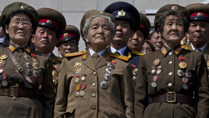 Retired North Korean military members stand at attention during an induction ceremony for children into the Korean Children's Union, the first political organization for North Koreans, held at a stadium in Pyongyang on Friday, April 12, 2013. (AP Photo/David Guttenfelder)