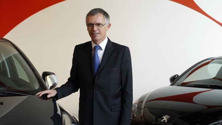 Carlos Tavares, Chief Executive Officer of French carmaker PSA Peugeot Citroen, poses next to a car after the company's 2014 First-Half results presentation at Peugeot headquarters in Paris