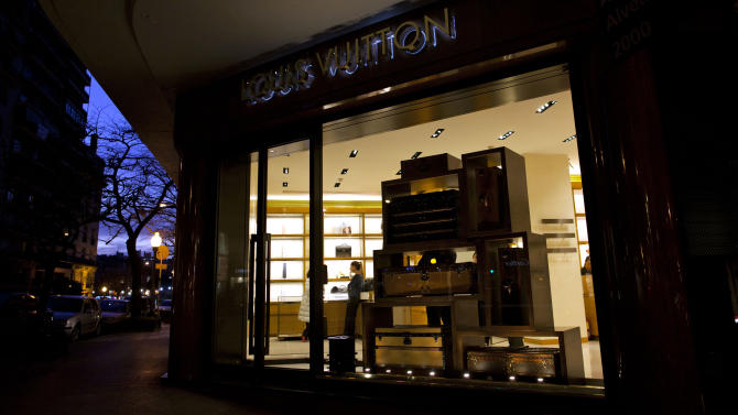 In this Sept. 26, 2012 photo, a vendor stands inside a Louis Vuitton store on Alvear Avenue in the Recoleta neighborhood of Buenos Aires, Argentina. French luxury conglomerate LVMH Moet Hennessy Louis Vuitton says on Thursday, Jan 31, 2013,  its net profit grew 12 percent. (AP Photo/Natacha Pisarenko)