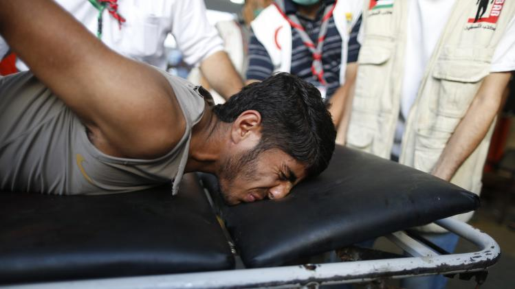 Palestinian, whom medics said was wounded in an Israeli air strike on a van, reacts as he is brought to at a hospital in Gaza City