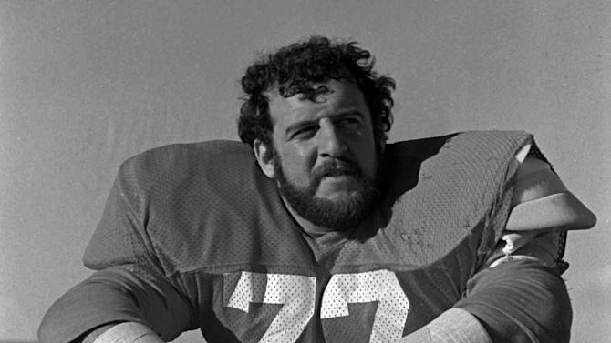 FILE - In this Nov. 25, 1977, file photo, Denver Bronco defensive lineman Lyle Alzado takes a break during practice as the NFL football team prepares to meet Baltimore. With uneven testing for steroids and inconsistent punishment, college football players are packing on significant weight _ in some cases, 30 pounds or more in a single year _ without drawing much attention from their schools or the NCAA in a sport that earns tens of billions of dollars for teams Football's most infamous steroid user was Alzado, who became a star NFL defensive end in the 1970s and 80s before he admitted to juicing his entire career. He started in college, where the 190-pound freshman gained 40 pounds in one year. It was a 21 percent jump in body mass, a tremendous gain that far exceeded what researchers have seen in controlled, short-term studies of steroid use by athletes. Alzado died of brain cancer in 1992.(AP photo)