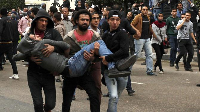 Anti-government protesters help an injured protester when pro-government protesters threw stones during a protest in Cairo