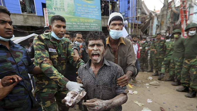 A Bangladeshi garment worker who soldiers said  was pulled alive from the rubble reacts as he walk on his own at the site of a building that collapsed Wednesday in Savar, near Dhaka, Bangladesh, Friday, April 26, 2013. By Friday, the death toll reached hundreds of people as rescuers continued to search for injured and missing, after a huge section of an eight-story building that housed several garment factories splintered into a pile of concrete.(AP Photo/Kevin Frayer)