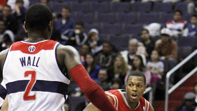 Houston Rockets point guard Kyle Lowry (7) dribbles toward Washington Wizards point guard John Wall (2) during the first quarter of an NBA basketball game at the Verizon Center in Washington, on Monday, Jan. 16, 2012. (AP Photo/Jacquelyn Martin)