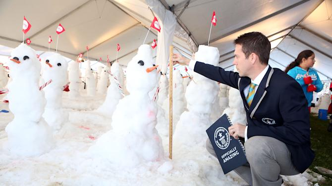 IMAGE DISTRIBUTED FOR MATTEL - Snowmen in Southern California are measured in an attempt to break the Guinness World Record for most snowmen built in one hour at Mattel Headquarters on Thurs., Dec. 13, 2012 in El Segundo, Calif. (Photo by Casey Rodgers/Invision for Mattel/AP Images)